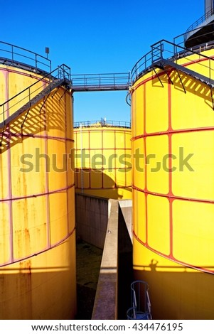 Old metal sheets l tanks in power plant, old kind of factory plant. Metal construction with old yellow paint and rusty places. Iron circle ladders around construction - stock photo