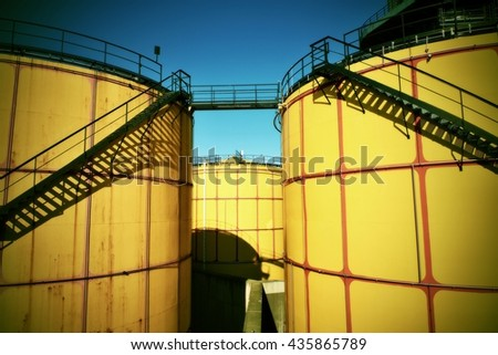 Old metal sheets l tanks in power plant, old kind of factory plant. Metal construction with old yellow paint and rusty places. Iron circle ladders around construction. Strong vignetting  effect. - stock photo