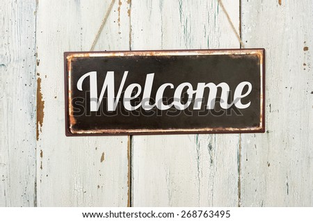 Old metal sign in front of a white wooden wall - Welcome - stock photo