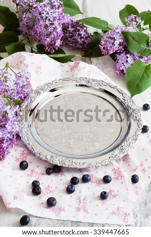 old metal tray, berries and lilac flowers on the holiday table. utensils and crockery - stock photo