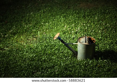 Old metal watering can on green grass at night in the spot of light. - stock photo