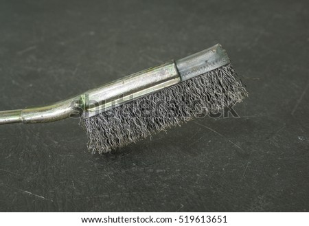 Old metal wire brush with steel handle on grey table