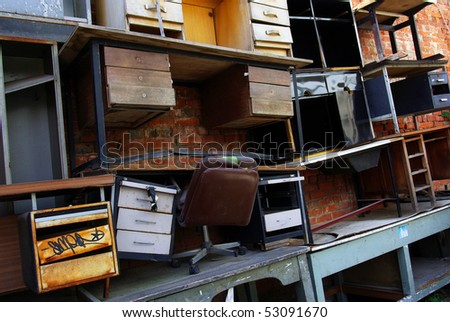Old metallic and wooden desks and chairs piled on top of each other - stock photo