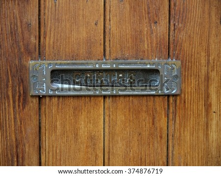 """Old metallic mailbox with text """"letters"""" in a wooden door - stock photo"""
