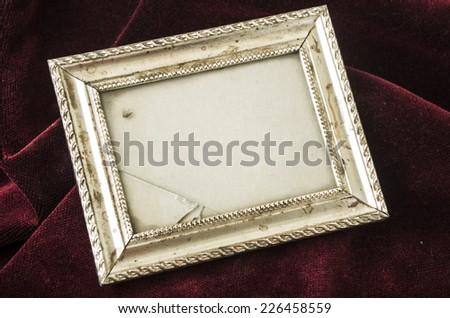 old metallic silver broken photo frame over red velvet textile - stock photo