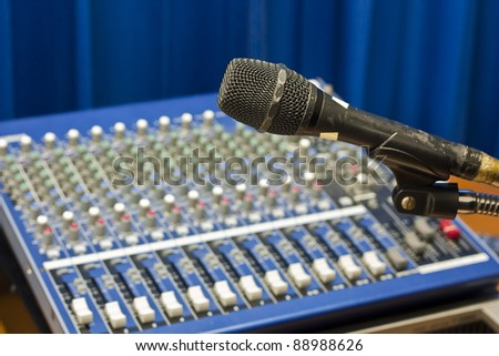 Old microphone on stand in front of sound mixer device - stock photo