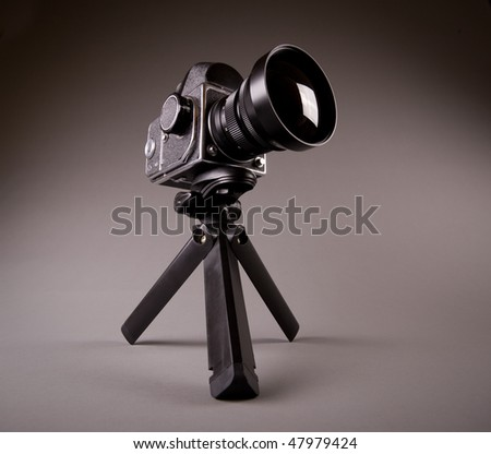Old middle format photo camera with tripod on grey in Hi-Res - stock photo