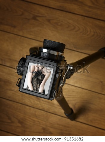 Old middle format photo camera with tripod on wooden floor - stock photo