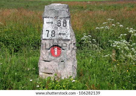 Old milestone made of granite by highway 110 (previously number 1) in Finland at summer. - stock photo