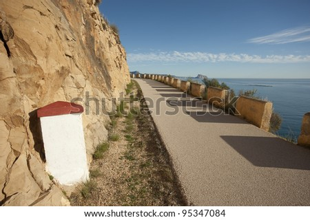 Old milestone on a scenic road above the Mediterranean - stock photo