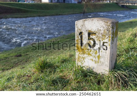 Old milestone on a sunny and lush green meadow at the shore of a small river near Freiburg, Germany - stock photo