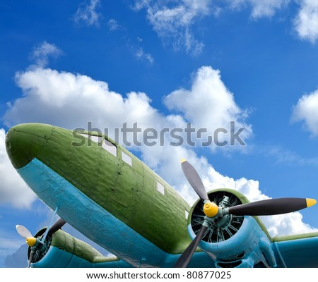 Old military aircraft against blue cloudy sky - stock photo