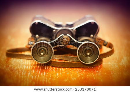 Old military binoculars on a bright orange background since the Second World War. retro thing - stock photo