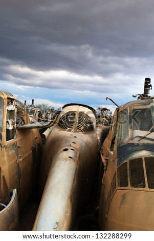 Old military helicopters await recycling in a junkyard - stock photo