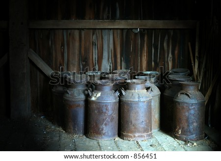 Old Milk Cans in a Barn - stock photo