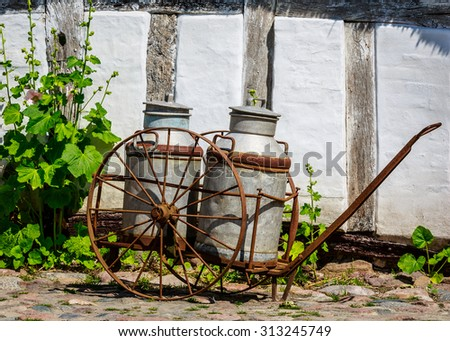 Old milk cans in rusty cart in front of white old timbered wall