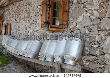 old milk cans on a shelve at a alpine hut - stock photo