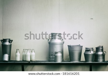 Old milk jugs, cans and bottles  - stock photo