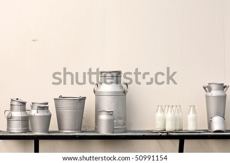 Old milk jugs, cans, bottles and bucket - stock photo