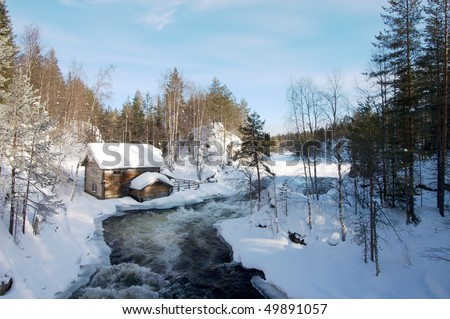Old mill by river in frozen winter landscape - stock photo
