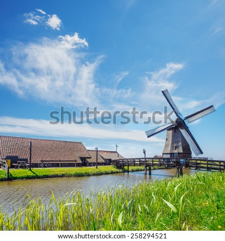 Old mill, farm houses and dyke, in the Netherlands, North Holland province - stock photo