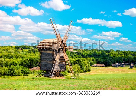 old mill from a wood on a sunny day in a green field with a blue sky, the filter - stock photo