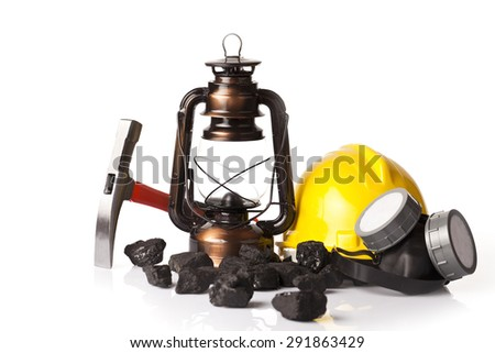 Old mining lamp with yellow helmet, mining pickax, dust mask and loose lumps of black coal - stock photo