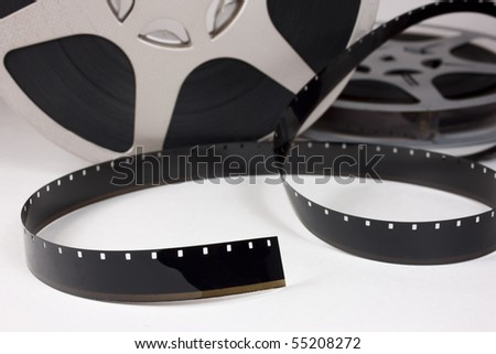 Old 16 mm movie film and reels. Focus on foreground film. - stock photo