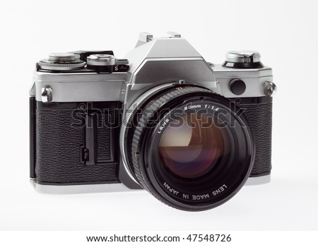 old 35mm SLR camera, angle view, on a white background. - stock photo