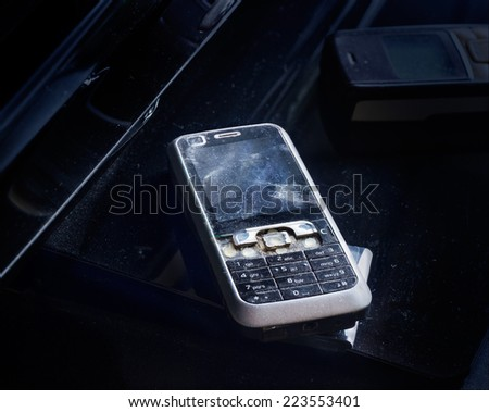 Old mobile phone broken and crack on dust dark background - stock photo