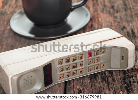 Old mobile phone put on wooden table with cup of coffee, Vintage tone style. - stock photo