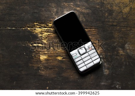 Old mobile phone  still life on the wood table - stock photo