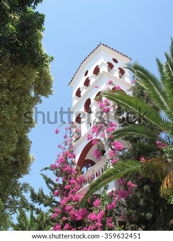 Old monastery of Saint George in Crete and pink flowers - stock photo