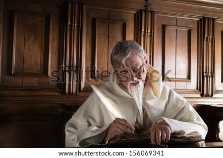 Old monk in habit writing with a feather quill