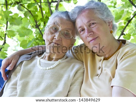 old mother and grandmother embracing - stock photo
