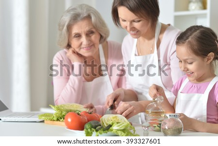 old mother and young daughter  in the kitchen - stock photo