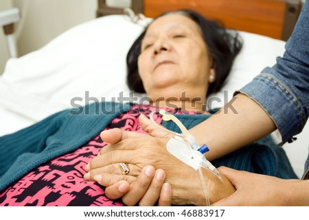 old mother sick in hospital. hand being hold by her caring daughter - stock photo