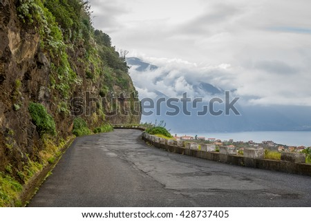 Old mountain road between steep mountain wall and cliff to the ocean. North coast of Madeira island, Portugal.