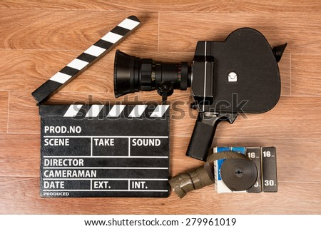 Old movie camera with a movie clapper and film. Preparations for shooting movie - stock photo