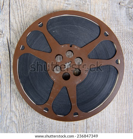 old movie film reel 16mm on the wooden table - stock photo