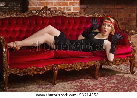 Old movies style: frightened woman lying on a sofa.
