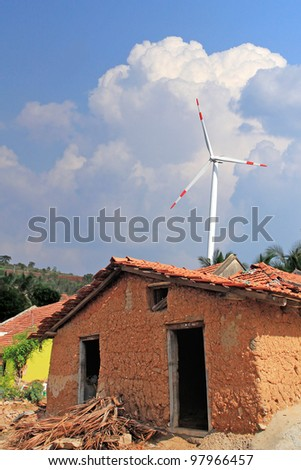 Old mud house in rural india with wind mill in the backdrop