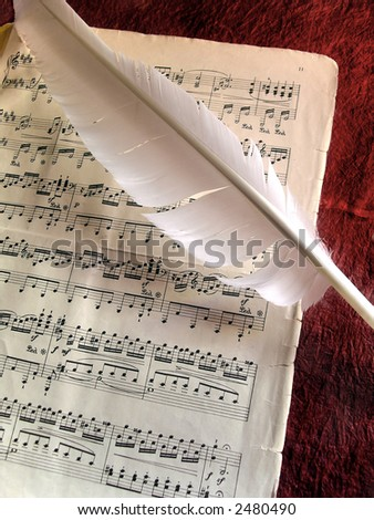 Old music partiture and white feather over red background - stock photo