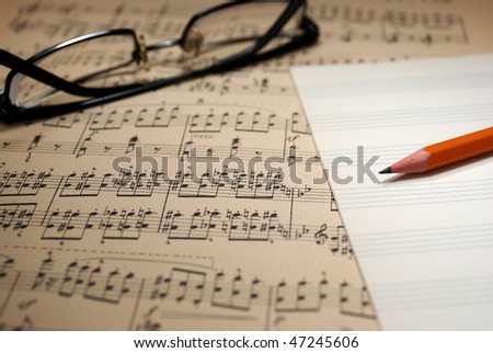 Old music sheet, music copybook, pencil and glasses.