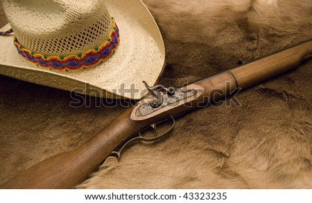 Old Muzzleloader and Hat with a colorful mayan band on top of an old deer skin - stock photo