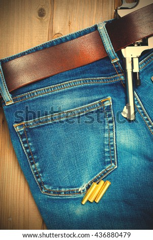 old nagan in his belt of blue jeans. instagram image filter retro style - stock photo