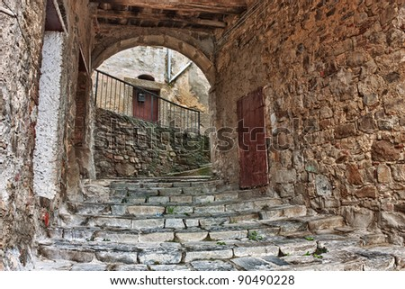 old narrow alley with staircase and vault in tuscan town - antique italian lane in Tuscany, Italy - stock photo