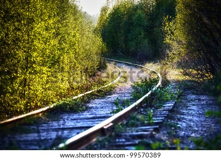old narrow railway in the forest at day - stock photo