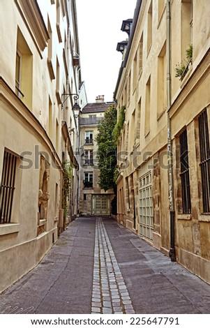 Old narrow street of Paris, France. - stock photo