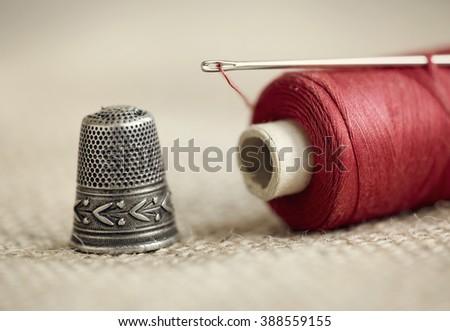 Old needle, thread and thimble  - stock photo